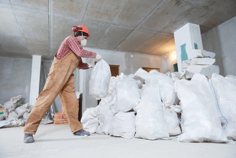 Arbetare som samlar konstruktionsavfalls i påse royaltyfri fotografi