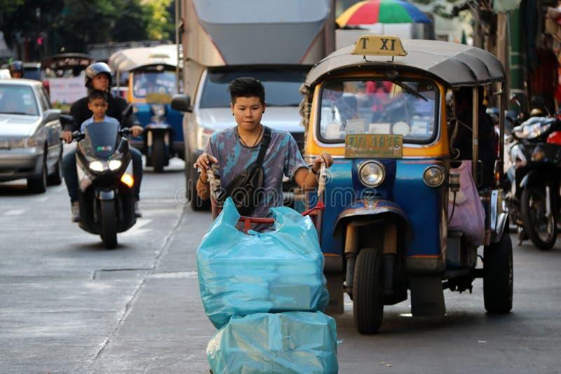 Arbetare som skjuter spårvagnen för två hjul på vägen till leveransvaroren på den Sampheng handelstaden, Bangkok, Thailand arkivbild