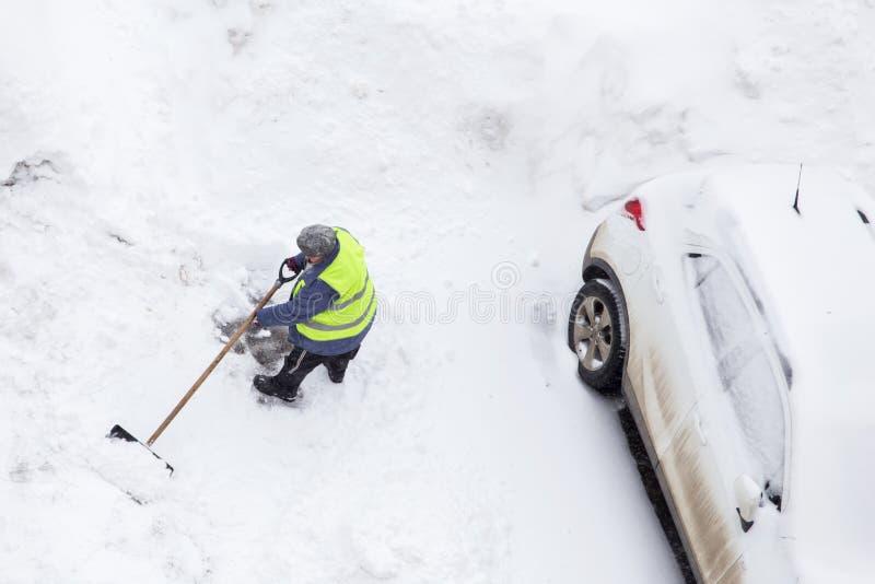 Arbetare som skyfflar snö nära bilar på parkering Top beskådar royaltyfria bilder