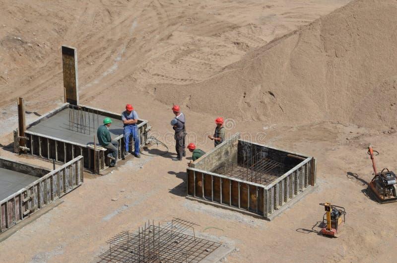 Arbetare som står på konstruktionsplatsen som har en konversation under paus arkivfoton