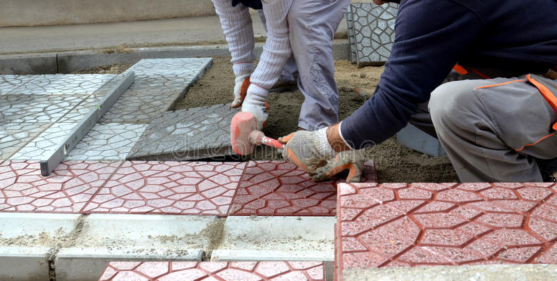Arbetare som stenlägger gångbanan arkivfoton