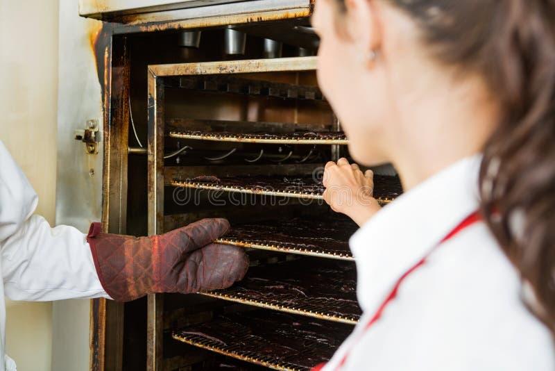 Arbetare som tar bort torkade köttskivor från Oven At arkivbilder