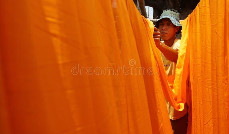 Arbetare som torkar tyg som används som materiell batik royaltyfria bilder