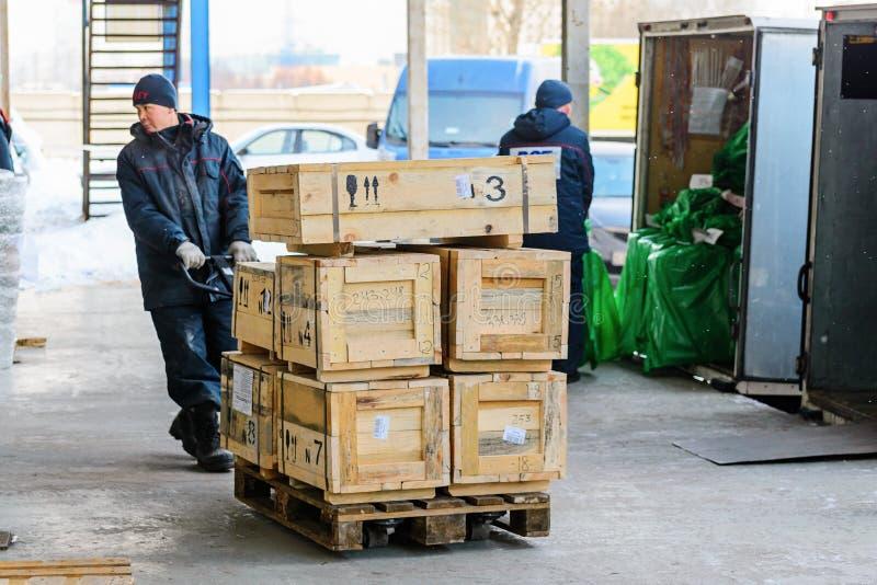 Arbetare som transporterar träaskar på en handspårvagn arkivbild