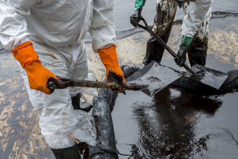 Arbetare tar bort råolja från en strand, råolja på oljeutsläpp royaltyfri fotografi