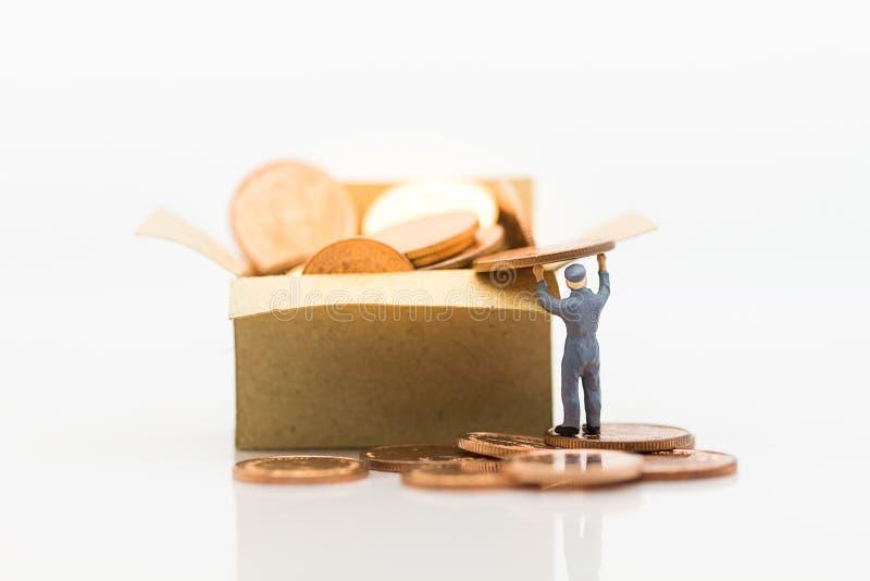 Arbetare tar mynt in i askar, askar mycket av mynt Bildbruk för affärsidéen, miniatyrfolk fotografering för bildbyråer