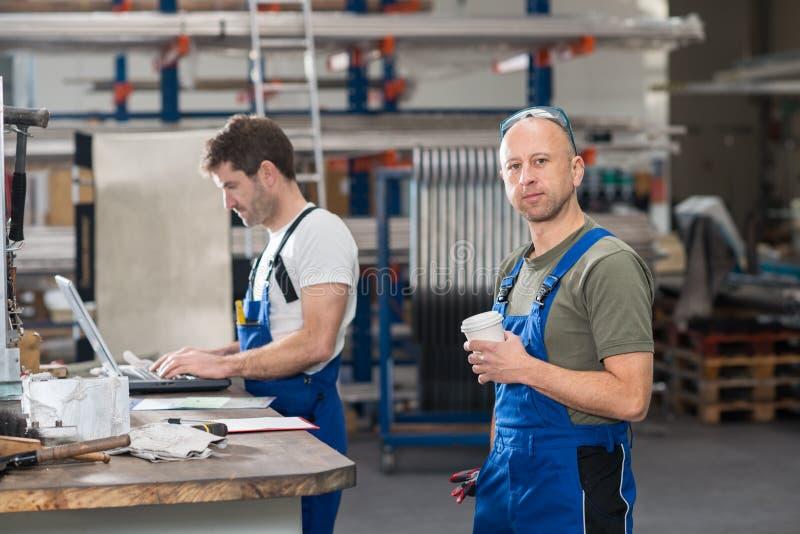 Arbetare två i fabrik arkivfoto