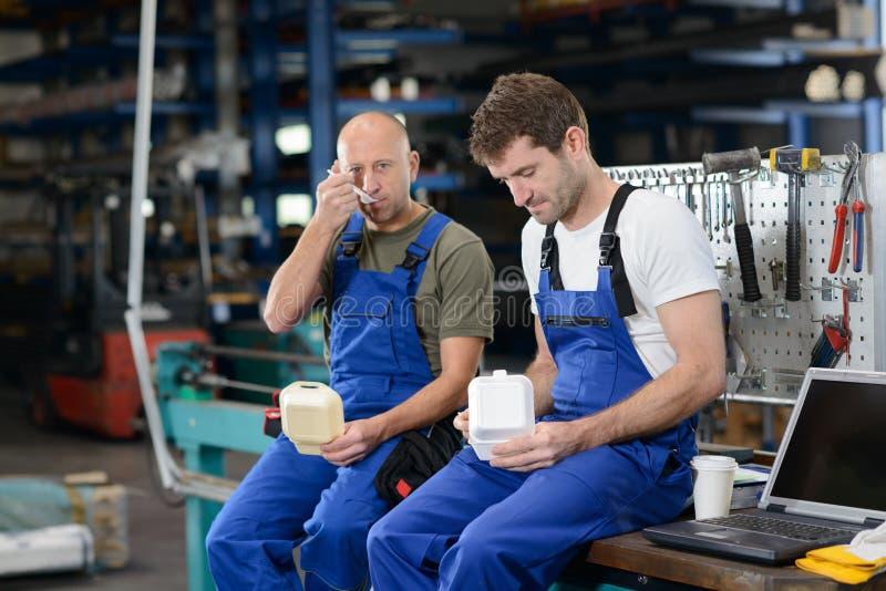Arbetare två i fabrik har ett avbrott royaltyfri fotografi