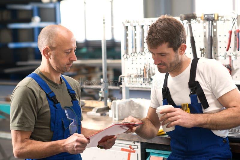 Arbetare två i fabrik i konversation arkivbild