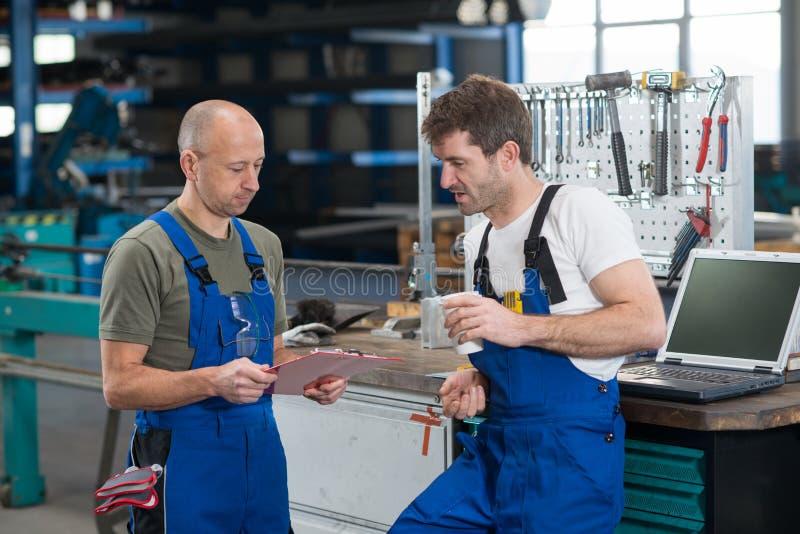 Arbetare två i fabrik i konversation royaltyfri foto