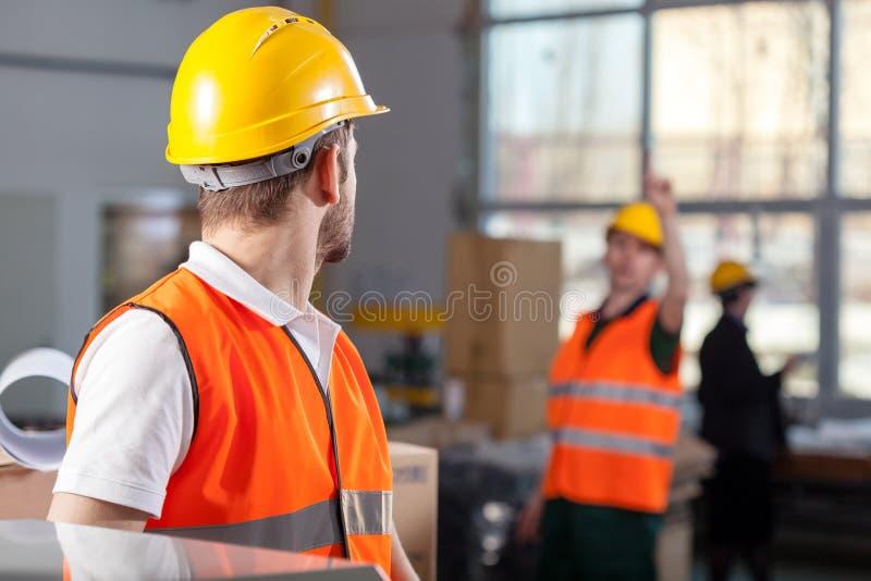 Arbetare under jobb i fabrik arkivfoto