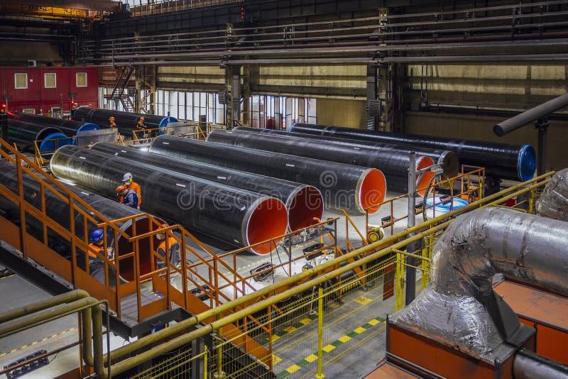 Arbetare undersöker det nya bestrukna röret i fabrik arkivbilder