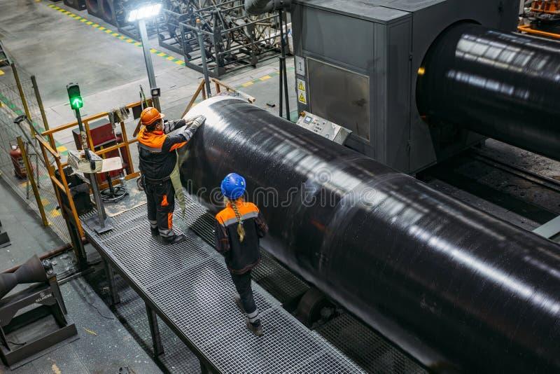 Arbetare undersöker det nya bestrukna röret i fabrik arkivbild
