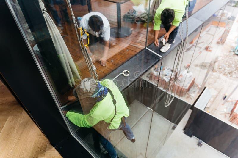 Arbetare utrustade säkerhetsselet för att arbeta på exponeringsglasfönster utanför byggnad royaltyfria foton