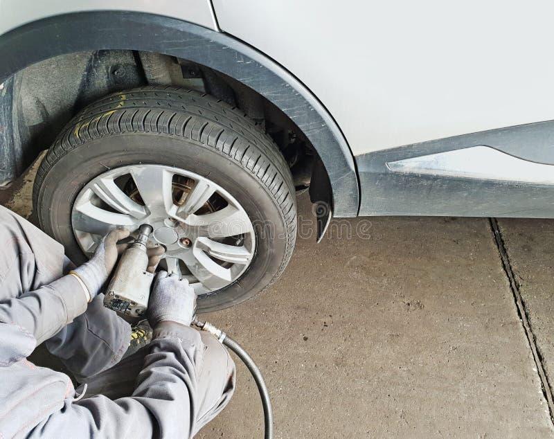 Arbetaren ändrar bilens gummihjul royaltyfria foton