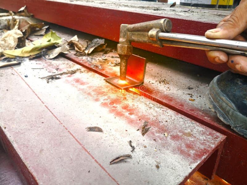 Arbetaren är stål för bitande fackla vid syre- och acetylenskäraren arkivfoton