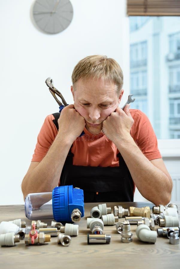 Arbetaren är tänka och se beståndsdelarna av rörmokerit royaltyfria bilder