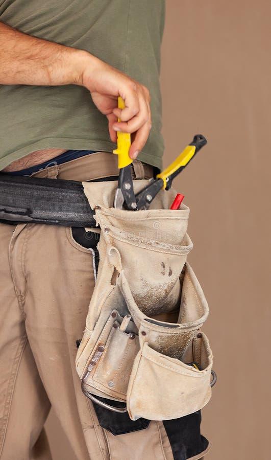 Arbetaren använder ögonblicket för bältet för hjälpmedlet autentisk och verklig, arkivfoto