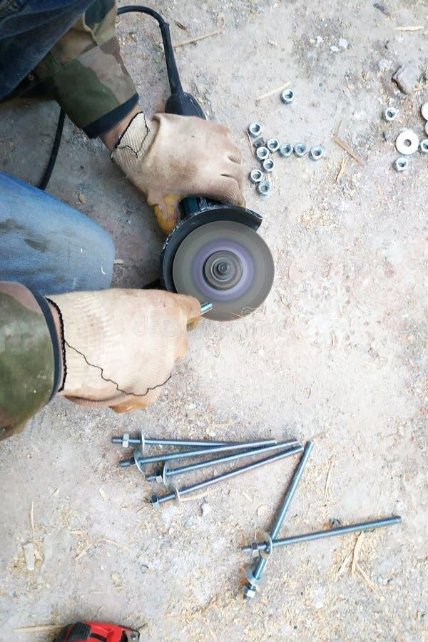 Arbetaren använder en vinkelmolar för att vässa bultarna, ett närbildplan royaltyfri foto