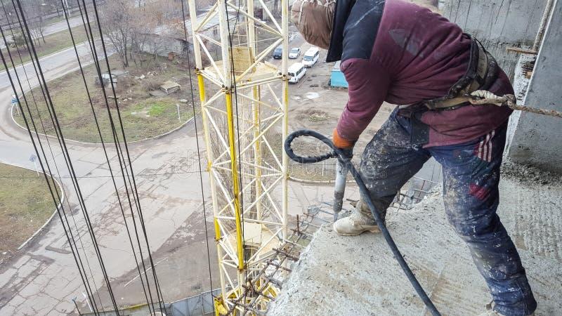Arbetaren arbetar på konstruktionsplatsen med en pneumatisk tryckluftsborr fotografering för bildbyråer