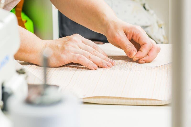 arbetaren av sömnadproduktion använder sax för att klippa av tyg fotografering för bildbyråer