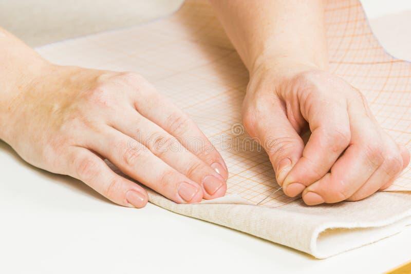 arbetaren av sömnadproduktion använder sax för att klippa av tyg arkivbilder