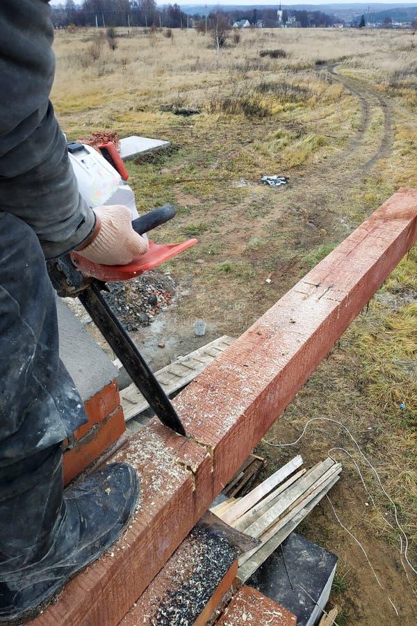 Arbetaren bär ut trä som bearbetar genom att använda chainsaws i konstruktionen av huset fotografering för bildbyråer