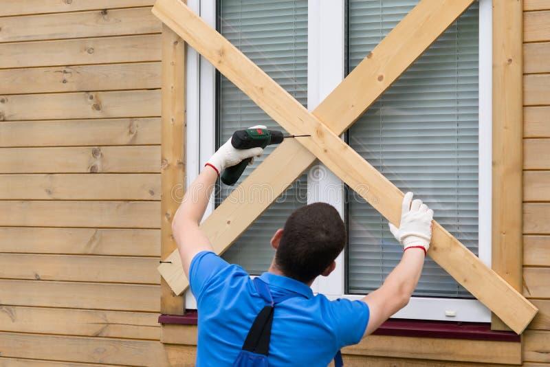 Arbetaren blockerar fönstren med bräden för att skydda dem från naturkatastrofer arkivfoton
