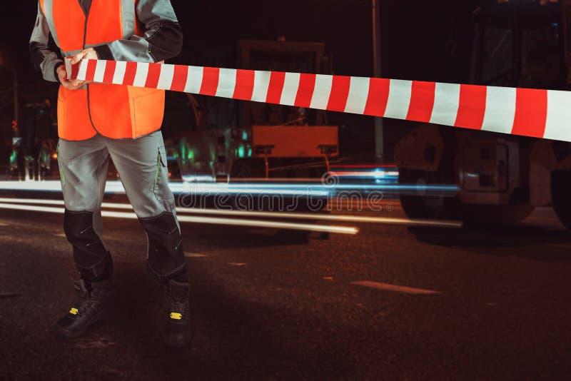 Arbetaren blockerar reparationsgatan arkivbilder