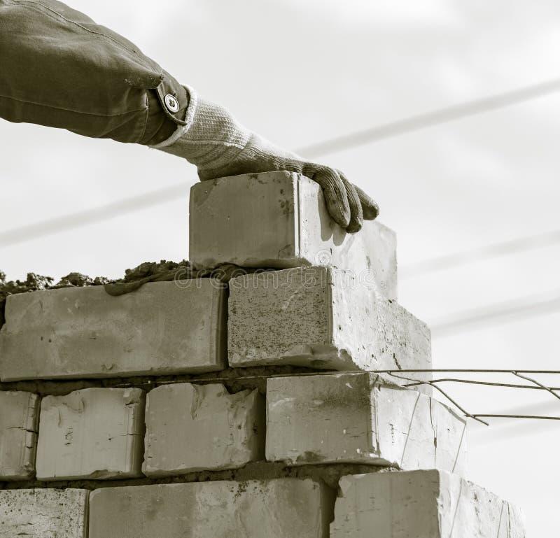 Arbetaren bygger en tegelstenvägg i huset arkivbild
