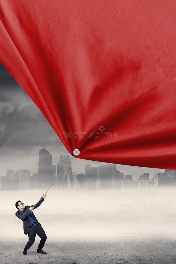 Arbetaren drar ett rött baner royaltyfri foto