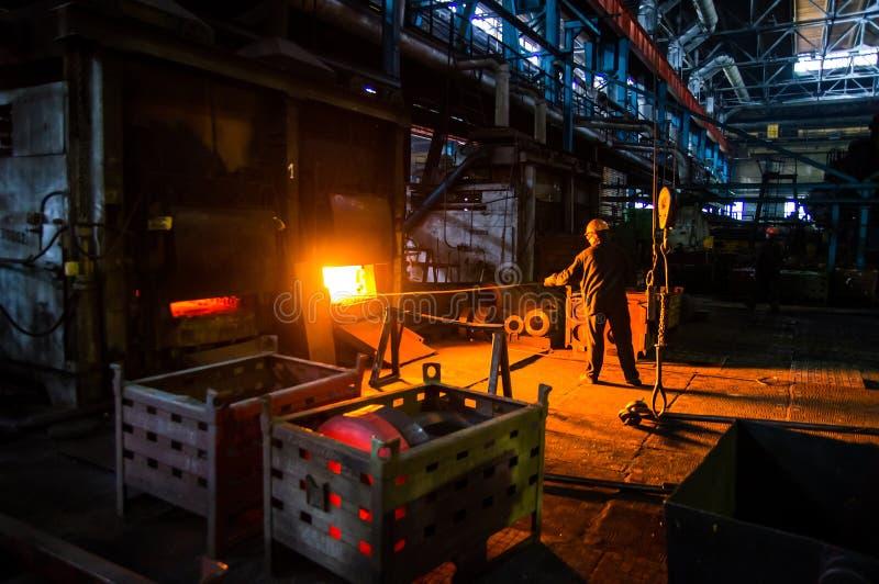Arbetaren drar workpiecen från ugnen royaltyfri fotografi