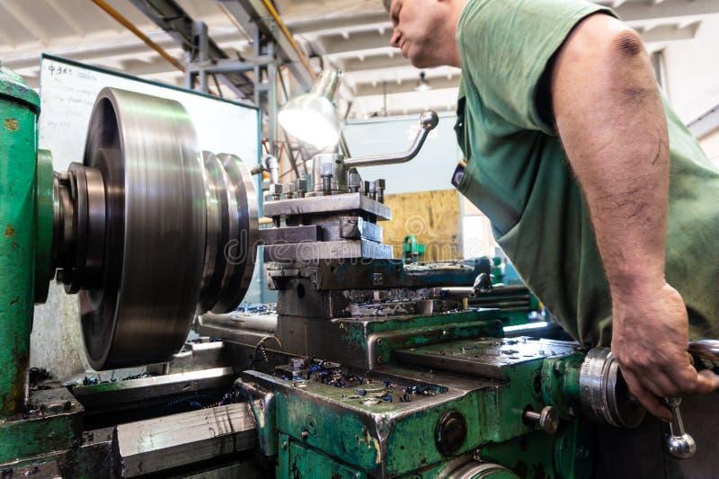 Arbetaren en man bearbetar metallprodukter på en maskin Roterande arbete i produktion royaltyfri bild