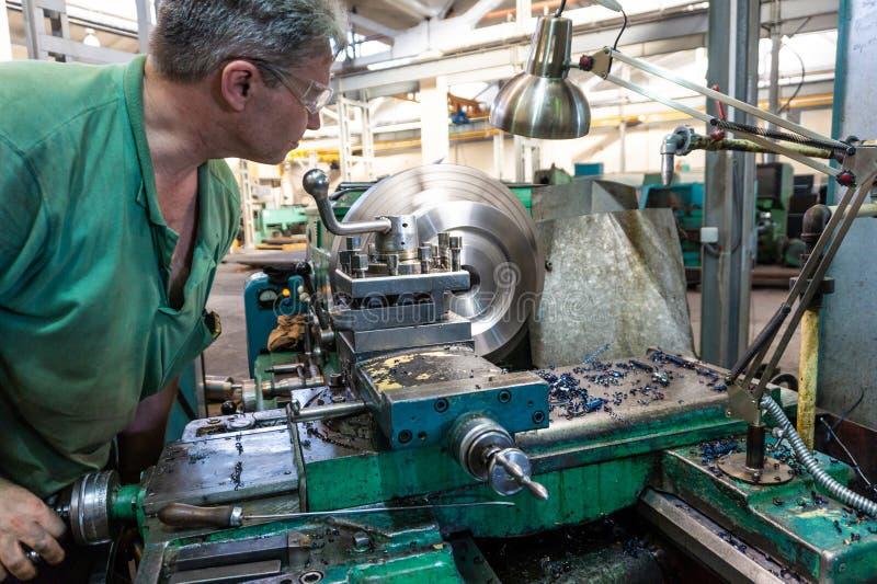 Arbetaren en man bearbetar metallprodukter på en maskin Roterande arbete i produktion royaltyfria bilder
