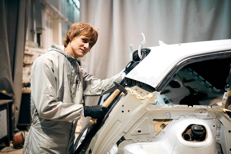 Arbetaren för den automatiska reparationen slätar och arrangera i rak linje metallkroppbilen med hammaren i garage ut arkivbild