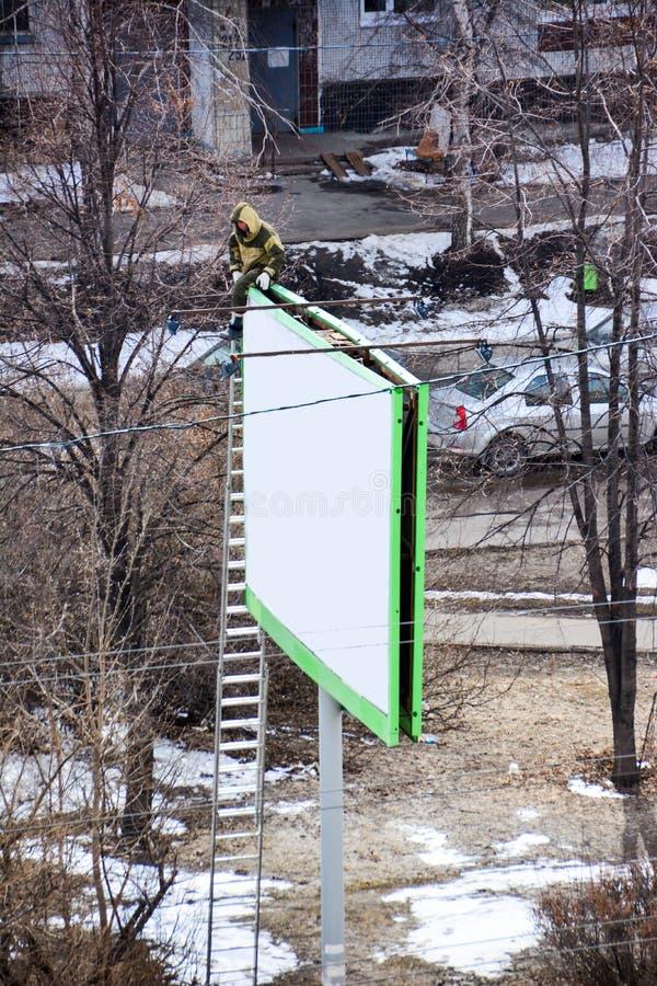 Arbetaren f?rbereder affischtavlan till installation av den nya annonseringen Industriell klättrare som arbetar på en stege - för arkivbild