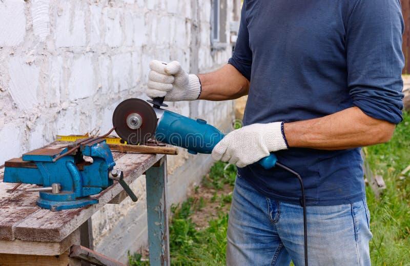 Arbetaren gör reparationer med elektriska hjälpmedel bultar och plattång i trädgård royaltyfri foto
