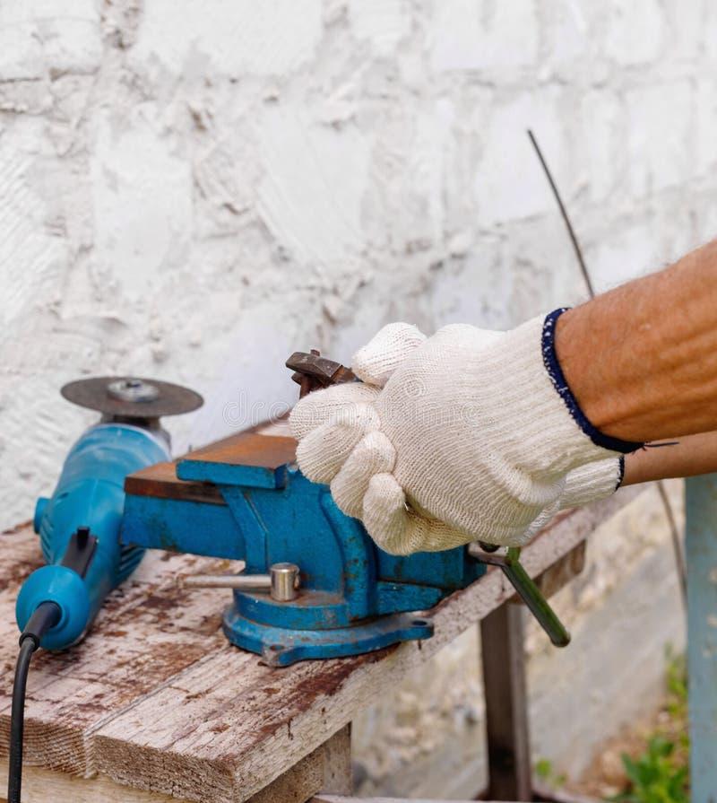Arbetaren gör reparationer med elektriska hjälpmedel bultar och plattång i trädgård av huset i utomhus- royaltyfria bilder