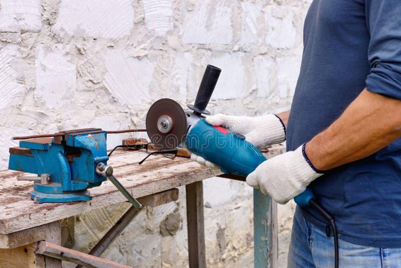 Arbetaren gör reparationer med elektriska hjälpmedel bultar och plattång i trädgård arkivbilder