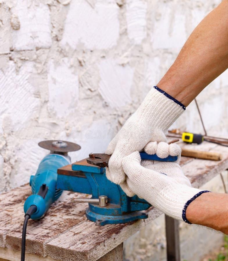 Arbetaren gör reparationer med elektriska hjälpmedel bultar och plattång i trädgård royaltyfri bild