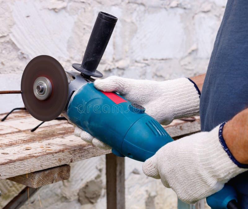 Arbetaren gör reparationer med elektriska hjälpmedel bultar och plattång i trädgård av huset i utomhus- arkivfoto