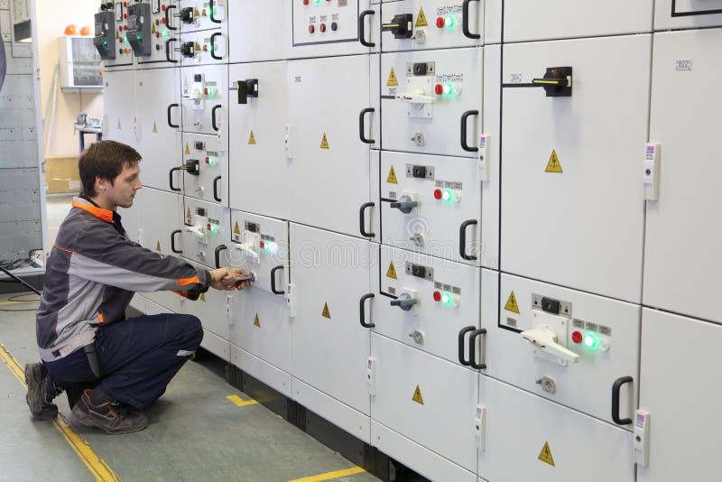 Arbetaren gör underhåll av elektrisk utrustning royaltyfria bilder
