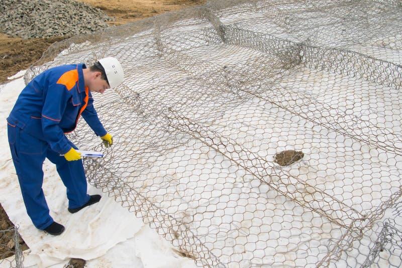 Arbetaren i blå likformig, kontrollerar cellerna i rastret för stenar, som planläggs för att förstärka bankerna av floden fotografering för bildbyråer