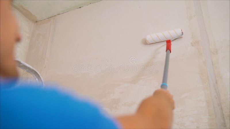 Arbetaren i en blå dräkt bearbetar väggen Arbetare som rappar en vägg Arbetare med en rulle arkivfoto