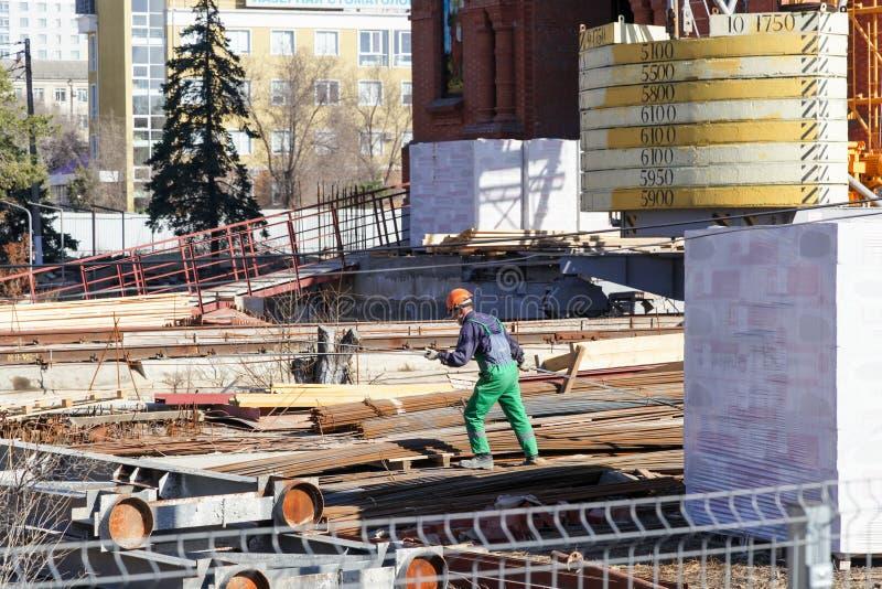 Arbetaren i en hjälm arbetar på byggnad royaltyfri foto