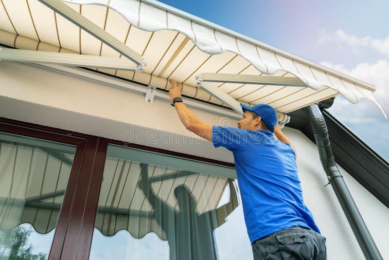 Arbetaren installerar en markis på husväggen över terrassen royaltyfri fotografi