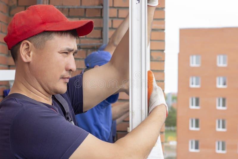 Arbetaren installerar fönster för att reparera i höghus royaltyfri foto