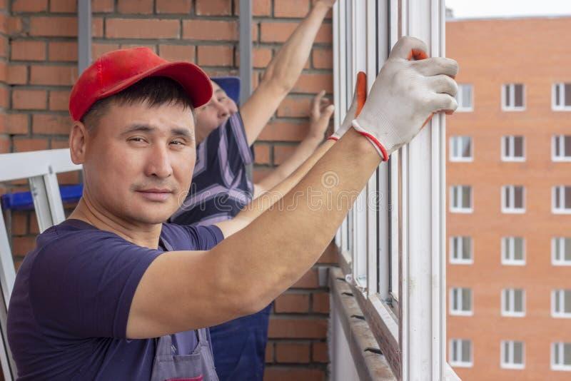 Arbetaren installerar fönster för att reparera i höghus arkivfoton