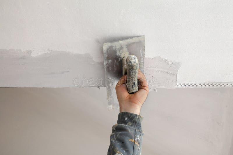 Arbetaren installerar plankan på taket och väggen arkivbild