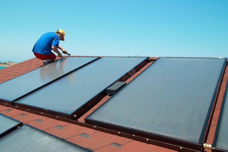 Arbetaren installerar solpaneler arkivbilder